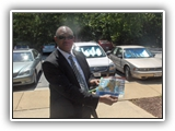 Photo of Gen Boroh showing a brochure for NAPKC.